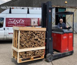 A fork lift truck carrying a pallet of fireplace logs